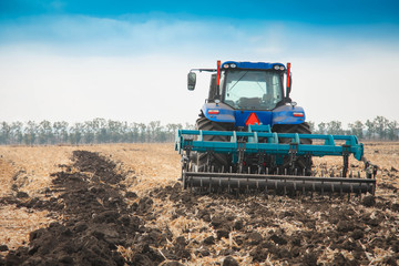 Wall Mural - A modern tractor on a plowed field on a clear day.