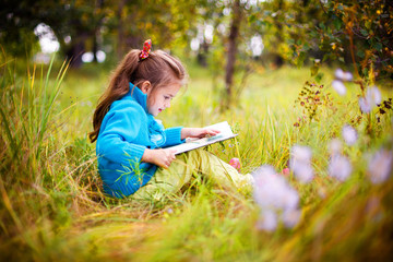 little girl in a blue sweater sits on the grass and reads a book