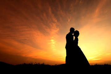 Silhouette two young lovers standing on the hill and kissing in wedding dress on sunset background