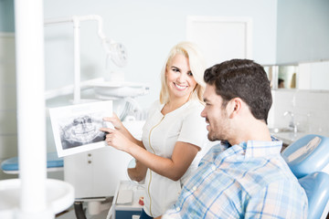 Female dentist showing x-rays to a patient