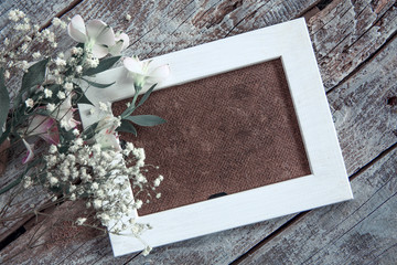 Blank photo frame and white flowers over wooden table background