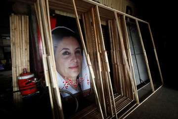 A poster of assassinated former Prime Minister Benazir Bhutto is seen behind wooden frames, manufactured to be used for campaigns of political parties outside a workshop ahead of general elections in Karachi