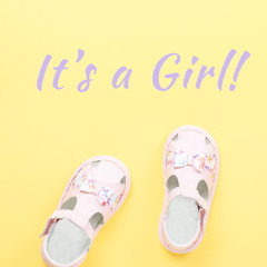 Pink baby girl summer sandals close up on yellow background with It's a girl text