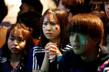 Japanese fans watch a broadcast of the World Cup Group H soccer match Japan vs Poland, at a sports bar in Tokyo