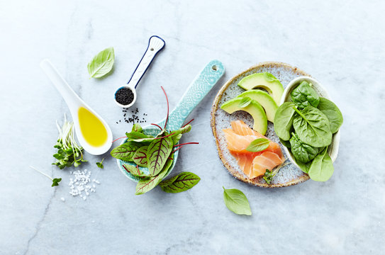 Ingredients for a healthy salad on gray stone background. Smoked salmon, avocado, spinach, sorrel, radihs sprouts, black cumin. Flat lay. Healthy diet.