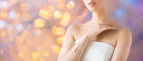beauty, jewelry and luxury concept - close up of beautiful woman with golden ring and bracelet over holidays lights background