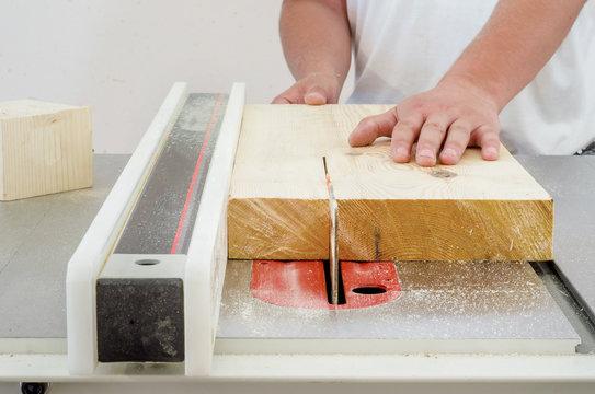Woodworking, a man cutting a board on a circular saw machine