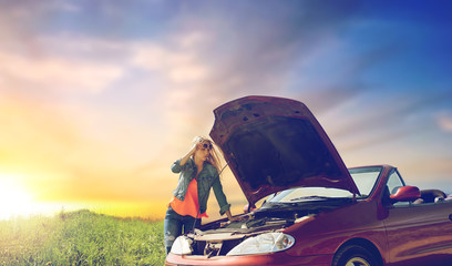 road trip, transport, travel and people concept - young woman with open hood of broken car at countryside over evening sky background