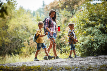 Mother and her little sons hiking trough forest .Outdoor leisure concept.