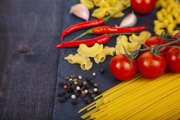 Different pasta on a  wooden background