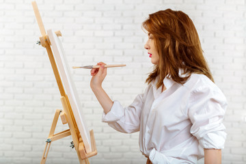 Beautiful young woman painter at work
