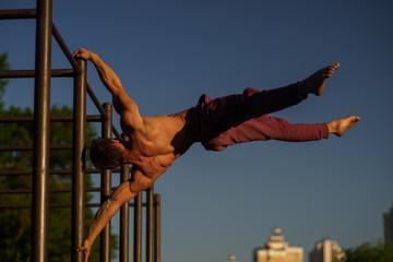 Foto auf Leinwand Gymnastik Muscular man making flag on the street. Street workout
