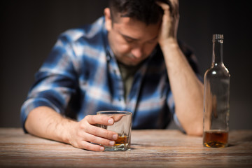 alcoholism, alcohol addiction and people concept - male alcoholic with bottle and glass drinking whiskey at night