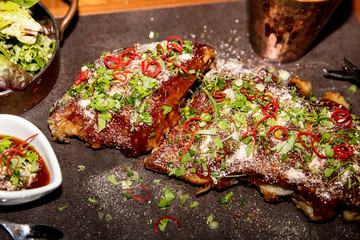 pork ribs cooked in thai style with spicy sauce and herbs