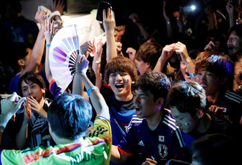 Japanese fans react after Japan progresses to the World Cup's last 16, after watching a broadcast of the World Cup Group H soccer match Japan vs Poland, at a sports bar in Tokyo