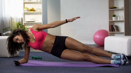 Mixed race woman doing side plank and using mobile phone, taking selfie photo