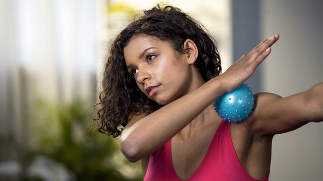 Attractive woman using massaging ball, muscles relaxation, blood circulation