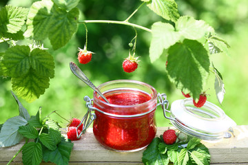Raspberry jam in a glass jar and fresh raspberry outdoors, selective focus