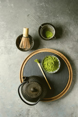 Ingredients for making matcha drink. Green tea matcha powder in ceramic bowl, traditional bamboo spoon and whisk on slate board, black iron teapot over grey texture background. Flat lay, space