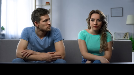 Stubborn girlfriend ignoring her guy silently watching tv, relationship crisis