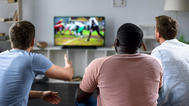 Male friends gather to watch football competition on big screen, sofa experts