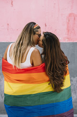 Lesbian couple wrap in gay pride flag kissing each other outdoors
