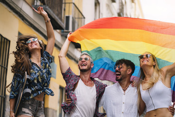 Group of gay friends with a gay pride flag on the street of Madrid city