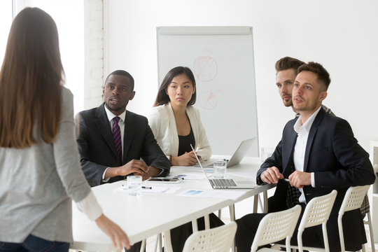 Diverse millennial team looking judgmental at female worker being late to meeting, angry colleague scolding unpunctual coworker for not coming on time to briefing. Punctuality, time management concept