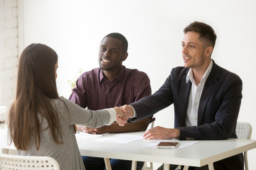 Multiethnic hr team welcoming female job candidate with handshake, male Caucasian employer shaking hand of woman applicant, greeting or congratulating with successful interview. Employment concept