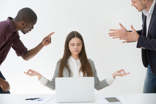 Calm female employee practicing yoga and meditating at workplace, ignoring multiracial colleagues shouting at her, blaming for business failure, woman relieving work stress. Emotion control concept