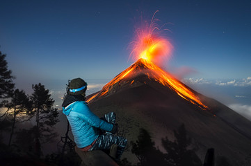 Female hiker watching eruption of Fuego Volcano, Guatemala