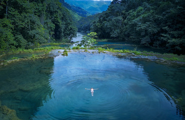 Woman in bikini floating on water in river at Semuc Champey, Guatemala