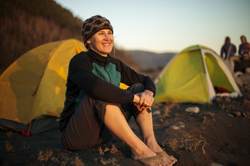 Smiling woman sitting near camping tent on beach, Big Flat, Lost Coast Trail, Kings Range National Conservation Area, California, USA