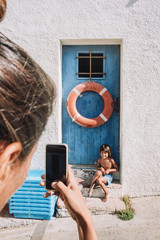 a mother takes a picture to her son with an iPhone in La Costa Brava