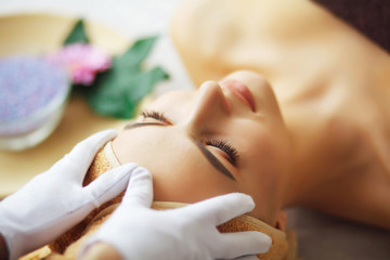 Beauty and Care. Spa Salon. Girl With Towel On Head. The Woman With Pure Skin Lying On The Massage Table And Relaxing. Skin Care. Cosmetologist Makes Skin Massage. High Resolution