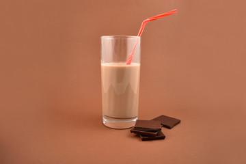 Chocolate milk stock images. Chocolate milk with chocolate pieces. Glass of chocolate milk on a brown background