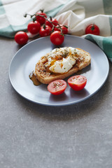 Boiled poached egg on a toast with cherry tomatoes on a blue plate over a grey stone  background. Vertical