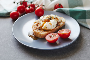 Boiled poached egg on a toast with cherry tomatoes on a blue plate over a grey stone  background. Tasty breakfast