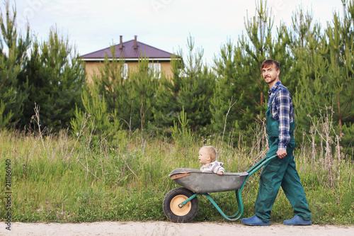 Happy Father In Working Uniform Pushing Son In Wheelbarrow