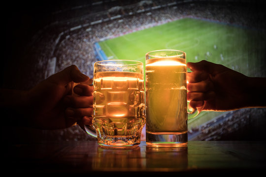 Two friends toasting (clinking) with glasses of light beer at the pub. Beautiful background with blurred view of playing game at the stadium.