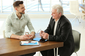 Two men consulting with each other in office