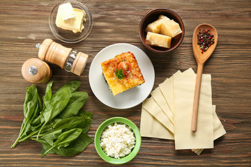 Composition of tasty lasagna with spinach on wooden background