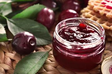 Small glass jar with tasty homemade plum jam on wicker mat