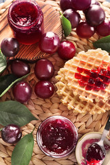 Composition with delicious homemade plum jam and waffles on wicker mat