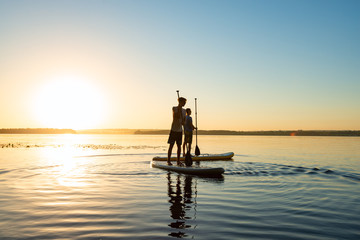 Men, friends relax on a SUP boards