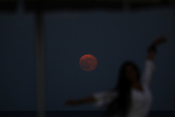 A woman poses for a picture in front of the moon, typically called a 'Strawberry Moon' when full in June, in Larnaca
