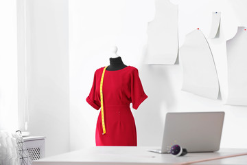 Mannequin with dress and measuring tape in tailor studio
