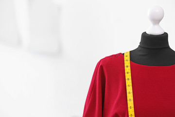 Mannequin with dress and measuring tape in tailor studio, closeup