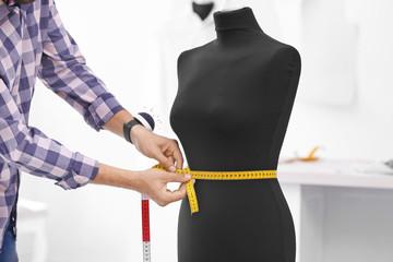 Tailor measuring mannequin in workshop, closeup