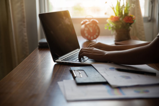 Business and finance concept. Financial adviser planning and working online on laptop, Business woman typing and review annual report at home. Annual report, clock on wooden table.